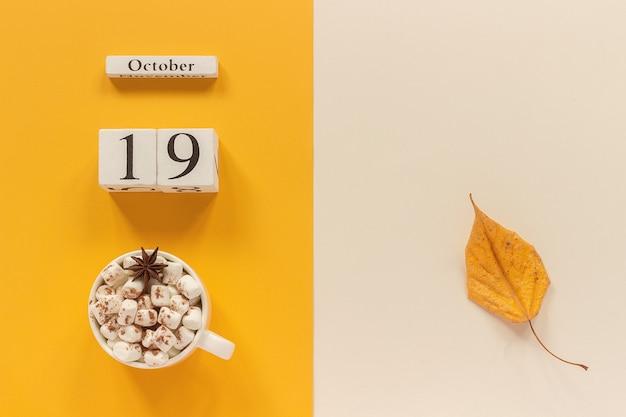 Herfst compositie. houten kalender 19 oktober, kopje cacao met marshmallows en gele herfstbladeren op gele beige achtergrond. bovenaanzicht plat lag mockup concept hallo september.