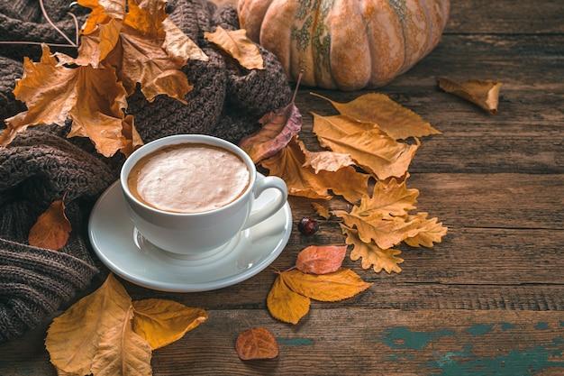Herfst compositie met koffie gebladerte pompoen en een trui op een houten achtergrond