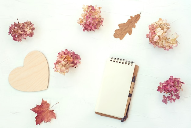 Herfst compositie met notebook en droge bloemen en bladeren