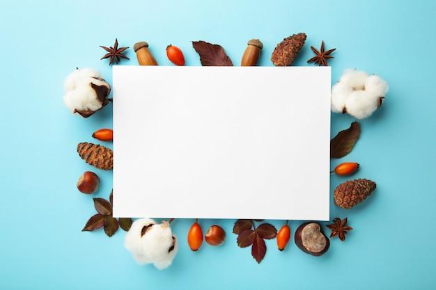 Herfst compositie. papier blanco met gedroogde bloemen en bladeren op blauwe achtergrond. herfst, herfstconcept. platliggend, bovenaanzicht, kopieerruimte, vierkant