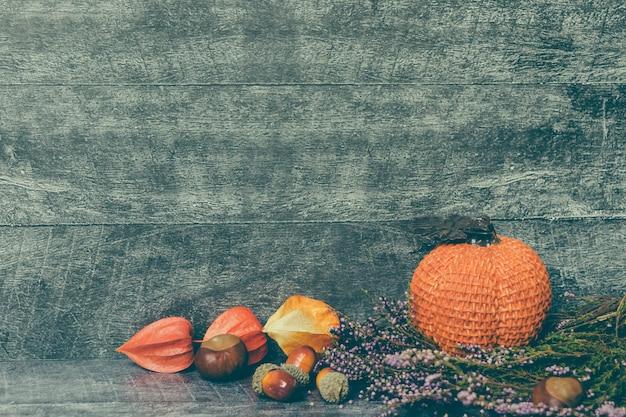 Herfst compositie. pompoen, gedroogde bladeren en physalis op houten ondergrond. herfst, herfst, halloween concept. platliggend, bovenaanzicht, kopieerruimte