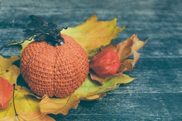 Herfst compositie. pompoen, gedroogde bladeren en physalis op houten ondergrond. herfst, herfst, halloween concept.
