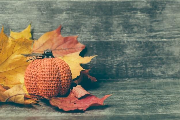 Herfst compositie. pompoen, gedroogde bladeren op pastel grijze achtergrond. herfst, herfst, halloween concept. platliggend, bovenaanzicht, kopieerruimte