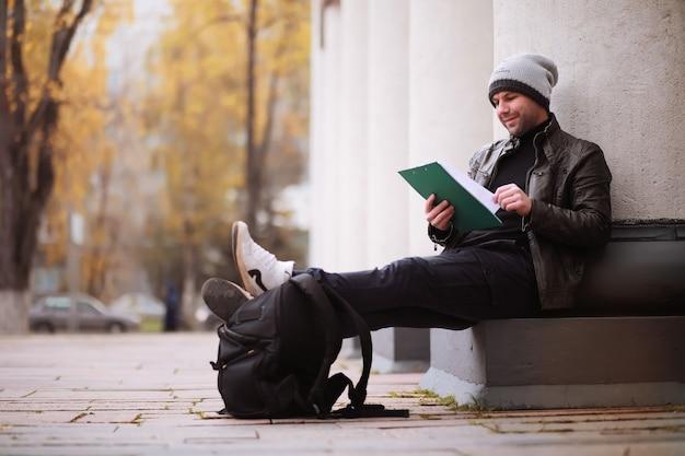 Herfst concept. een man loopt door de stad. herfstbladeren op voetpad. een