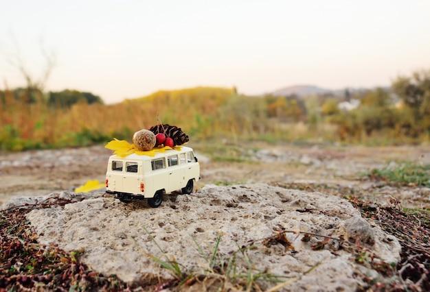 Herfst concept - een speelgoedauto gereden op het dak van eikels, rowan bessen, geel blad en een bult