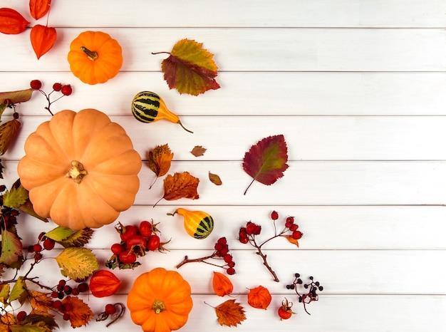 Herfst decor van pompoenen, bessen en bladeren op een witte houten achtergrond. concept van thanksgiving day of halloween. platliggende herfstcompositie met kopieerruimte.
