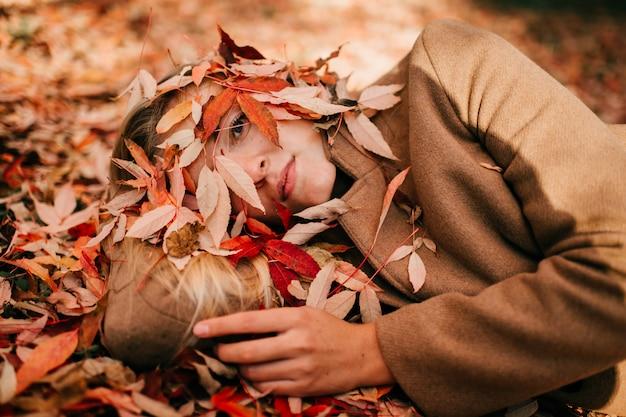 Herfst depressie. mooi jong meisje in wol bruine jas liggend op de grond met droevige melancholische ogen. zaken geklede vrouw die met vermoeid gezicht ziek kijken.