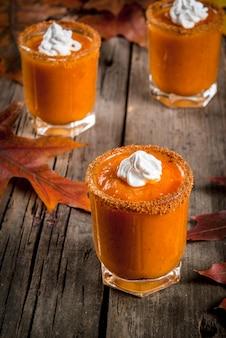 Herfst drankje. ideeën en recepten voor thanksgiving, halloween. alcohol cocktail pumpkin pie vodka shots op oude rustieke houten tafel met herfstbladeren, kopie ruimte