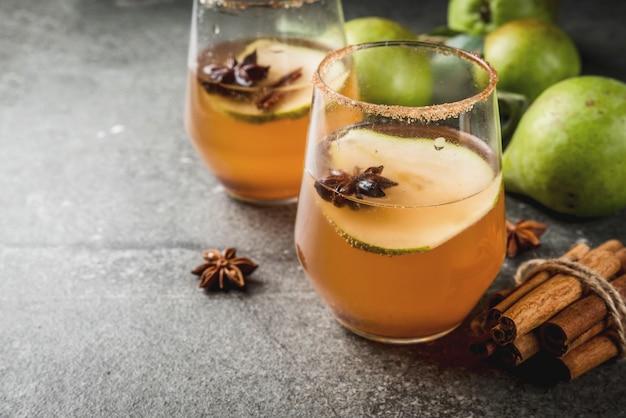 Herfst drankjes. glühwein. traditionele herfst kruidige cocktail met peer, cider en chocoladesiroop, met kaneel, anijs, bruine suiker. op zwarte stenen tafel. copyspace