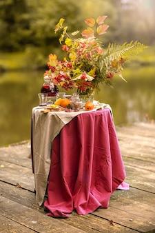 Herfst. een tafel aan de oevers van het meer versierd met een boeket herfstbladeren. theekransje. fruit thee met citroen, appels.