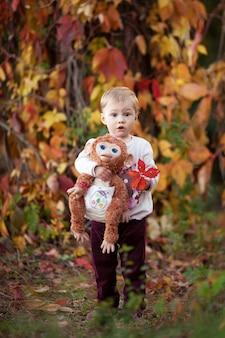 Herfst emotioneel portret van meisje. mooi klein meisje met aap speelgoed in herfst park. herfstactiviteiten voor kinderen. halloween en thanksgiving tijd plezier voor familie.
