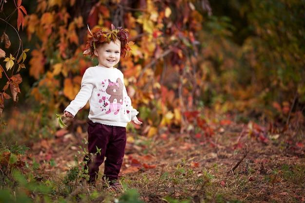 Herfst emotioneel portret van meisje. mooi klein meisje met rode druivenbladeren in de herfstpark. herfstactiviteiten voor kinderen. halloween en thanksgiving tijd plezier voor familie. ruimte kopiëren