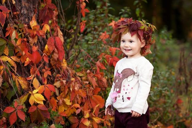 Herfst emotioneel portret van meisje. mooi klein meisje met rode druivenbladeren in de herfstpark. herfstactiviteiten voor kinderen. halloween en thanksgiving tijd plezier voor familie.