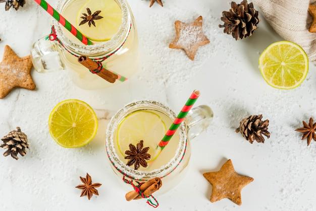 Herfst en winter drankjes. kerstvakantie drank. feestelijke sneeuwbalcocktail met limoensap, kaneel, likeur, suiker en anijssterren. op witte tafel met kerstdecoratie, copyspace bovenaanzicht