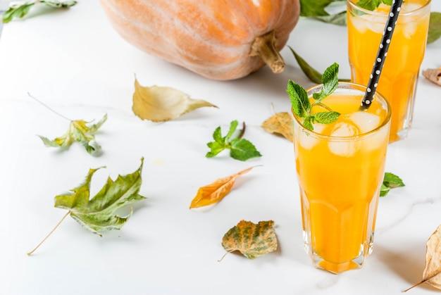 Herfst en winter koude cocktails. pittige pompoenmojito met verse munt, op witte marmeren tafel. kopie ruimte