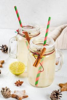 Herfst- en winterdranken. kerstvakantie drank. feestelijke sneeuwbalcocktail met limoensap, kaneel, likeur, suiker en anijssterren. op witte tafel met kerstdecoratie