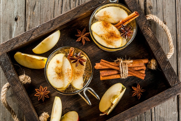 Herfst- en winterdranken. traditionele zelfgemaakte appelcider, cocktail van cider met aromatische kruiden - kaneel en anijs. op een oude houten rustieke tafel, op een dienblad. kopieer ruimte bovenaanzicht