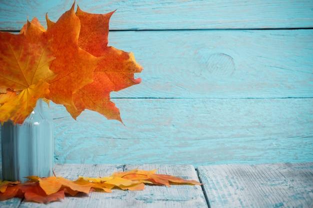 Herfst esdoorn bladeren bos in vaas op blauwe houten tafel