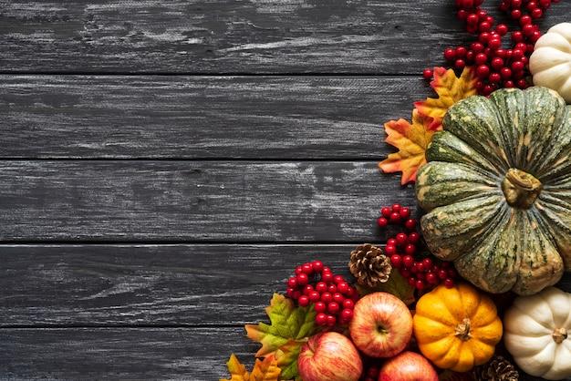 Herfst esdoorn bladeren met pompoen en rode bessen op oude houten.