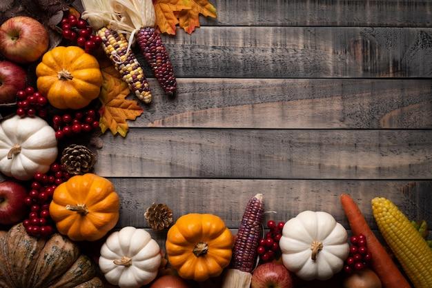 Herfst esdoorn bladeren met pompoen, maïs en rode bessen
