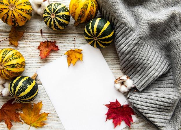Herfst esdoorn bladeren, pompoenen en wollen sjaal op een houten