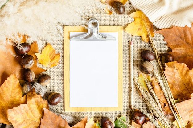 Herfst esdoorn bladeren, witboek lijst, potlood en kastanjes liggend op een bruin.