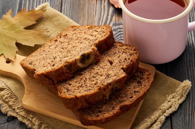 Herfst eten-plakjes bananenbrood, een kopje thee, droge bladeren, een donkere houten tafel. zijaanzicht.