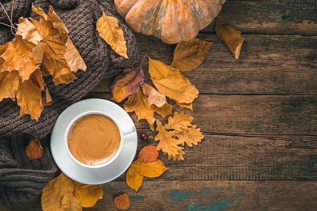 Herfst feestelijke achtergrond met een kopje koffie bladeren en een pompoen op een houten achtergrond
