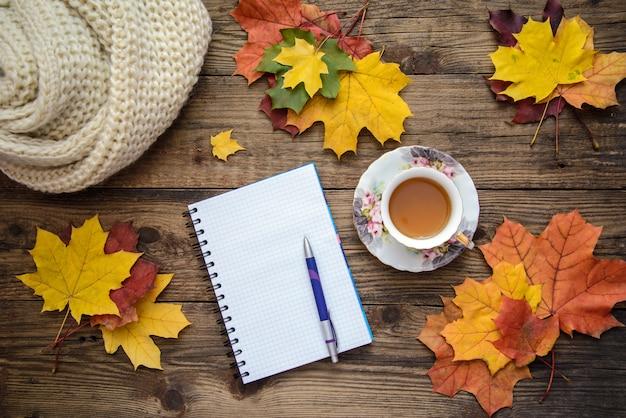 Herfst foto van gele bladeren, een kopje thee, een sjaal en een stuk papier met pen op houten achtergrond