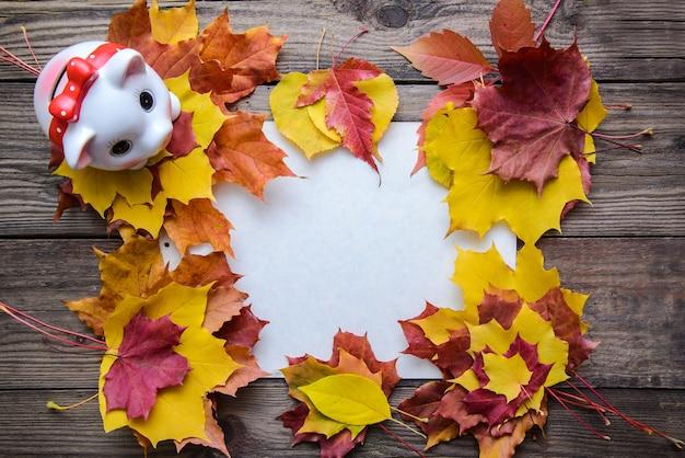 Herfst frame met gele, oranje, rode bladeren en spaarvarken op houten achtergrond met kopie ruimte