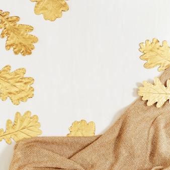 Herfst frame van gouden bladeren van de eik op lichte achtergrond en beige gebreide kleding.