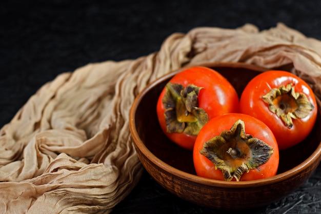 Herfst fruit. dadelpruim op een zwarte houten oppervlak. dadelpruimen in een kleiplaat.