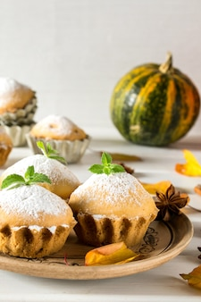 Herfst gebakjes. zelfgemaakte cupcakes met poedersuiker met kaneelstokjes, anijssterren, pompoenen, bessen van rozenbottel en herfstbladeren