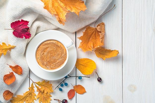 Herfst gebladerte cappuccino en een trui op een lichte achtergrond feestelijke herfst achtergrond