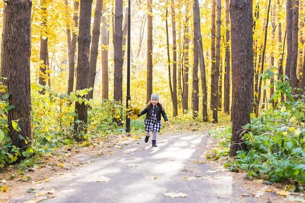Herfst, geluk en mensen concept - kind loopt door herfstpark met gele bladeren in haar handen.