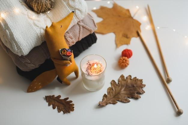Herfst gezellig stilleven en huisdecor met speelgoed, kaarsen en bladeren. dank concept