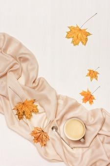 Herfst gezellige compositie met gedroogde bladeren van esdoorn en pastel beige sjaal, kopje koffie op witte houten achtergrond.