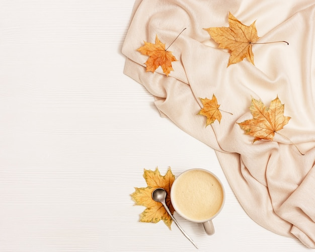Herfst gezellige compositie met gedroogde bladeren van esdoorn en pastel beige sjaal, kopje koffie