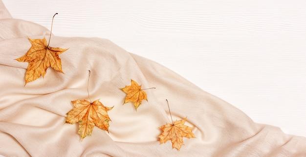 Herfst gezellige compositie met gedroogde bladeren van esdoorn en pastel beige sjaal op wit