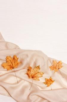 Herfst gezellige compositie met gedroogde bladeren van esdoorn en pastel beige sjaal op witte houten achtergrond. herfst, herfst concept. plat lag, bovenaanzicht, kopie ruimte.