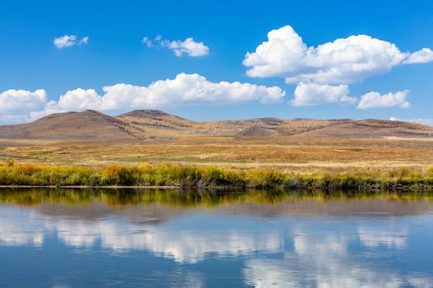 Herfst grasland onder blauwe lucht en witte wolken