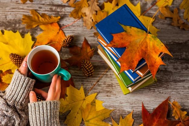 Herfst. handen met een kopje thee. boeken kleurrijk.