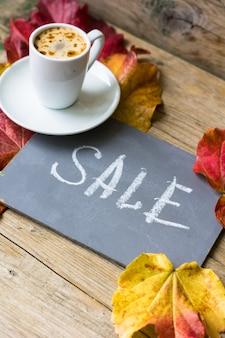 Herfst heldere bladerenachtergrond met bord en koffie