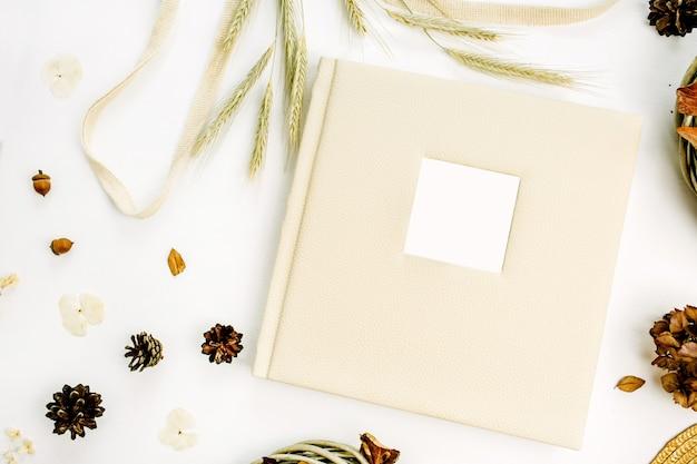 Herfst herfst compositie met bruiloft of familie fotoalbum, krans frame, string slecht, rogge oren, kegels, droge bladeren, strooien hoed op wit oppervlak