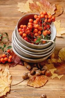 Herfst herfst seizoensgebonden samenstelling met stapel keramische kommen, gele esdoornbladeren, lijsterbessen, kastanjes en decoratieve pompoenen over houten tafel.