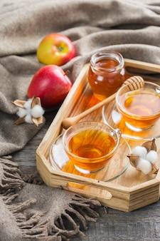 Herfst, herfst, winter interieur in hygge-stijl met drankje. seizoenssamenstelling met kop hete thee met honing, warme wollen sjaal, zachte plaid op een rustieke houten tafel.
