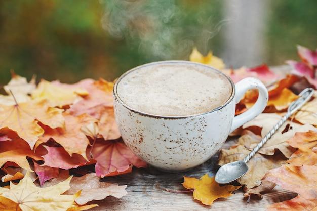 Herfst, herfstbladeren, heet dampende kop koffie.