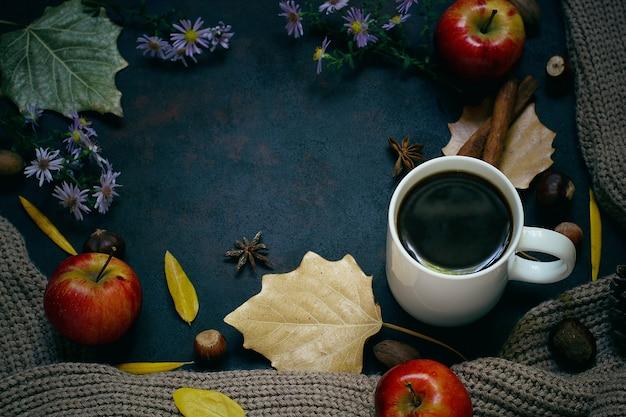 Herfst, herfstbladeren, hete dampende kop koffie en een warme sjaal of vest. seizoensgebonden, ochtendkoffie, zondag ontspannend en stillevenconcept.