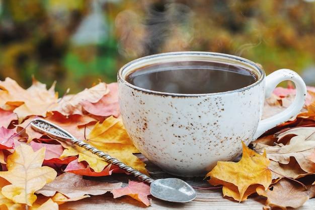 Herfst, herfstbladeren, hete dampende kop koffie.