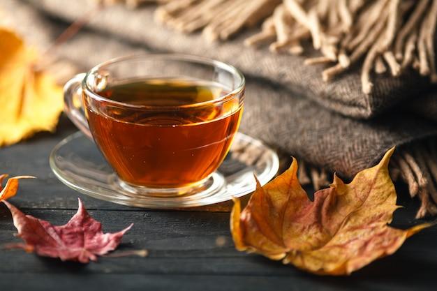 Herfst, herfstbladeren, warme kop koffie en een warme sjaal op houten tafel oppervlak. seizoensgebonden koffie in de ochtend, zondag ontspannen en stilleven concept.